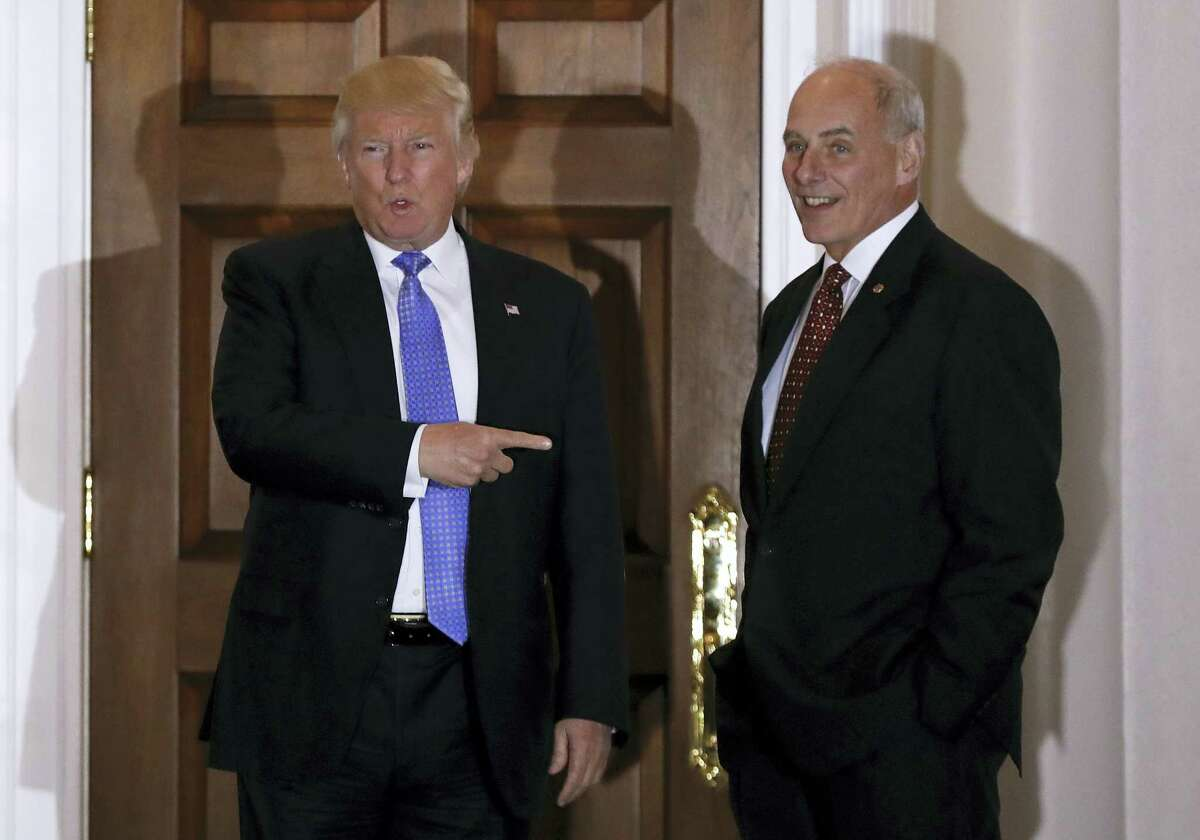 President-elect Donald Trump talks to media as he stands with National Security Adviser-designate, retired Marine Gen. John Kelly at the Trump National Golf Club Bedminster clubhouse in Bedminster, N.J.