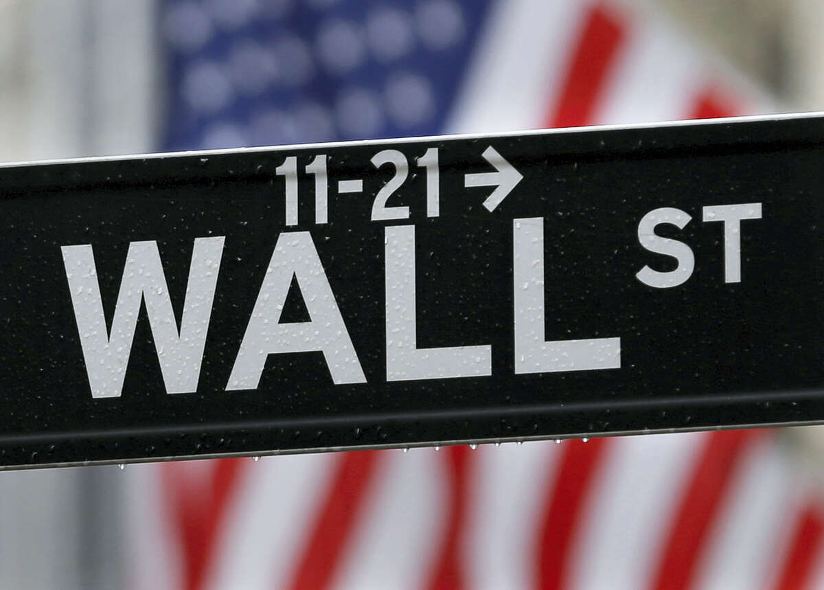 This photo shows a Wall Street sign near the New York Stock Exchange in New York. Global stocks wavered Friday as investors looked to see if the three major U.S. indexes can add to their record close as well as upcoming retail sales figures.