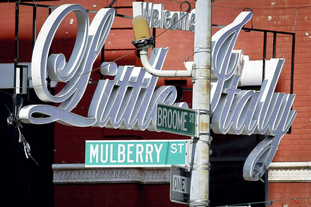 In this Aug. 9, 2016 photo, an overhead sign welcomes visitors to Little Italy at the corner of Broome and Mulberry Streets, in New York.