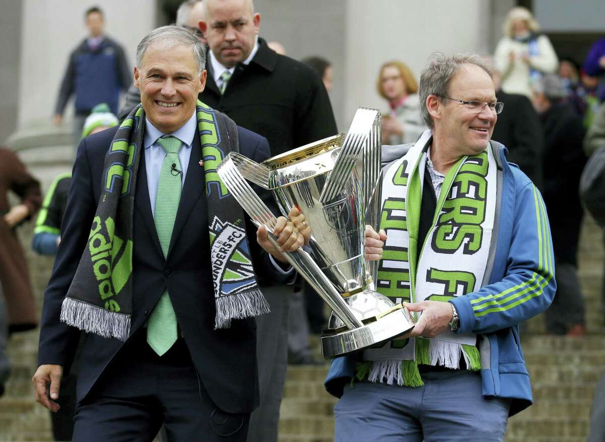 Seattle Sounders head coach Brian Schmetzer carries the MLS Cup trophy as he walks with Washington Gov. Jay Inslee, Wednesday in Olympia, Wash.