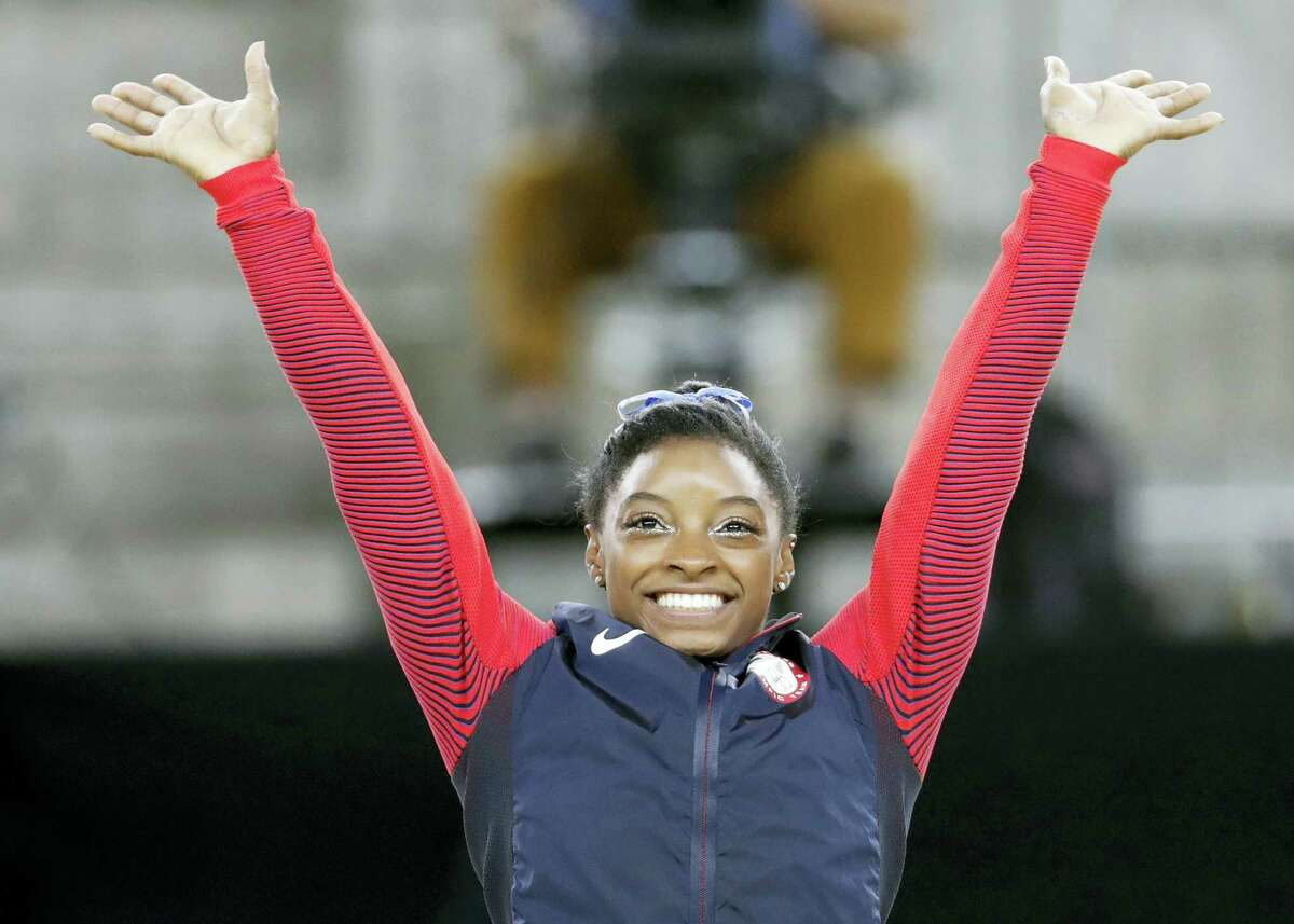 Gold medallist United States' Simone Biles waves on the podium during the artistic gymnastics women's individual all-around final at the 2016 Summer Olympics in Rio de Janeiro, Brazil, Thursday.