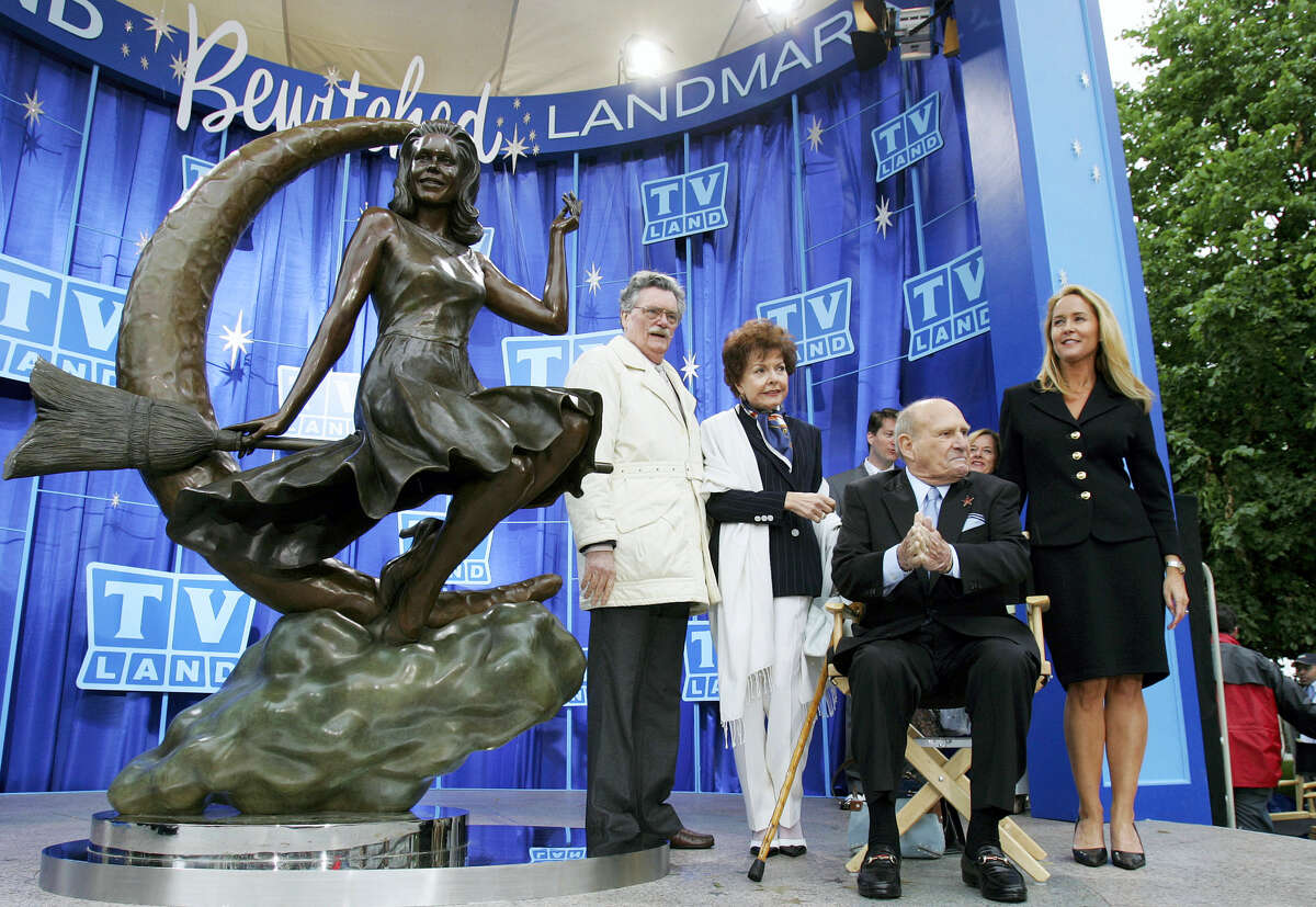 "Director of the 1960s sitcom 'Bewitched', Willaim Asher, seated, shares the stage with characters from the show, standing from left, Bernard Fox, Casey Rogers and Erin Murphy, in Salem, Mass., during the unveiling of a statue, left, depicting Samantha Stevens, the fictional witch played by Elizabeth Montgomery in the series. Fox, the mustachioed actor known to TV viewers as Dr. Bombay on ""Bewitched"" and Col. Crittendon on ""Hogan's Heroes,"" has died. He was 89. Harlan Boll, a spokesman for Fox's family, said he died Wednesday, Dec. 14, 2016, of heart failure at a Los Angeles-area hospital."