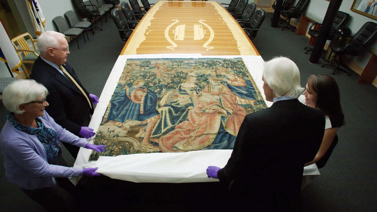 """This Nov. 7, 2016, image from video provided by HISTORY Canada & More4 shows a 16th century tapestry at the National WWII Museum in New Orleans that had been in Adolf Hitler's retreat in the Bavarian Alps. Looking at the tapestry are Dr. Nick Mueller, top left, and Toni Kiser, right, both from the museum, Cathy Hinz, bottom left, the daughter of Lt. Col. Paul Danahy, the American officer who took the tapestry from Hitler's Eagle's Nest in 1945, and Robert Edsel, presenter of the television documentary series """"Hunting Nazi Treasure."""" On Friday, Dec. 16, 2016, the tapestry, purchased for Hitler's Eagle's Nest a year before the war began from an art gallery in Munich owned by a Jewish family, will be formally returned to Germany in a ceremony."""