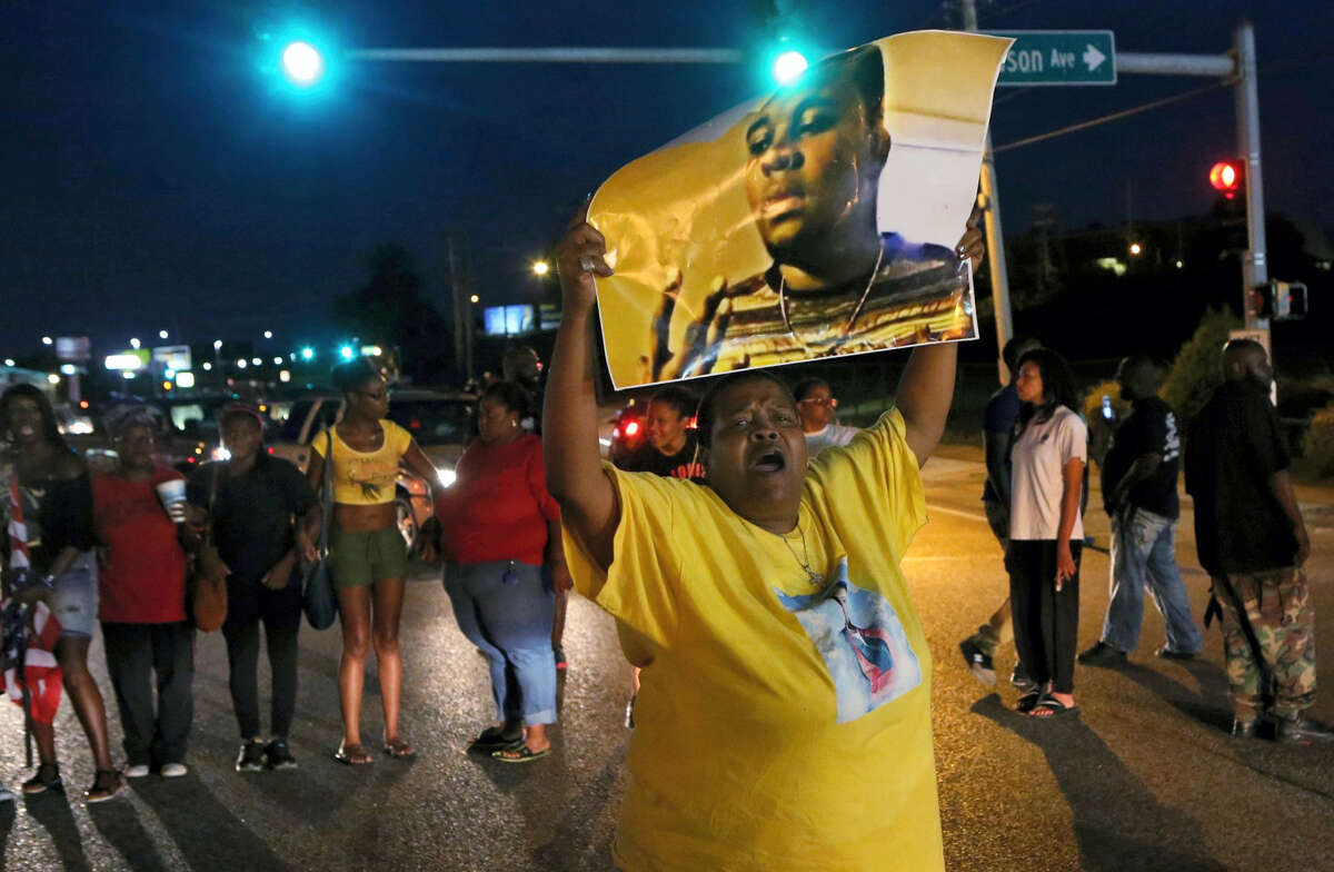 Sharon Cowan chants as she marches Tuesday, Aug. 9, 2016, in Ferguson, Mo., on the second anniversary of the death of Michael Brown, an unarmed black 18-year-old who was shoot by a white police officer. (J.B. Forbes/St. Louis Post-Dispatch via AP)
