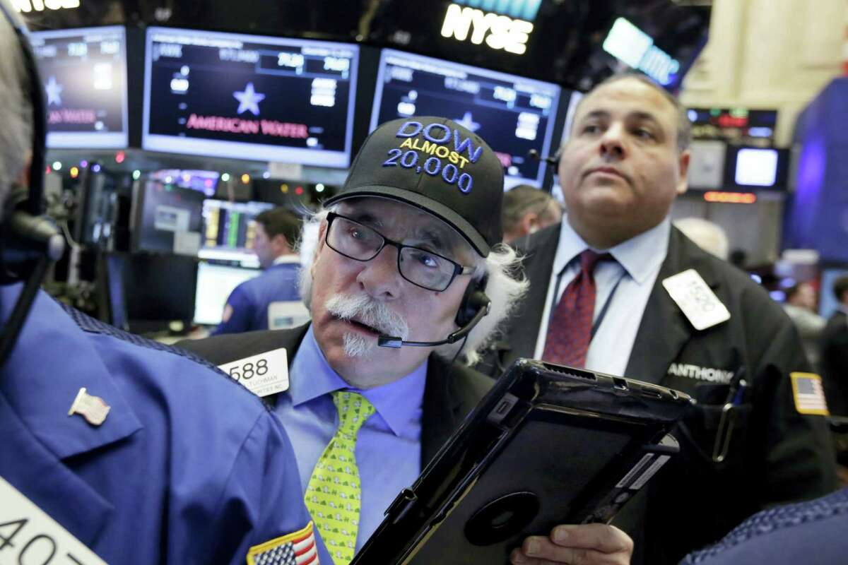 """Trader Peter Tuchman wears his """"Dow Almost 20,000"""" cap as he works on the floor of the New York Stock Exchange Thursday."""