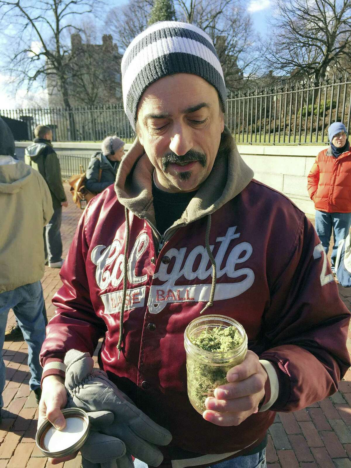 Keith Saunders, a marijuana activist from Scituate, Mass., holds a jar that he says contains just under an ounce of pot, now legal in Massachusetts. Advocates gathered in front of the Massachusetts Statehouse Thursday to celebrate the voter-approved law legalizing the recreational use of marijuana that took effect at midnight Thursday.
