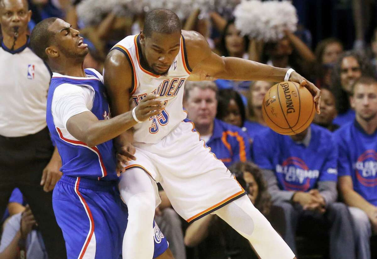 Oklahoma City Thunder forward Kevin Durant, right, drives against Los Angeles Clippers guard Chris Paul, left, in the second quarter of Game 1 of the Western Conference semifinal NBA basketball playoff series in Oklahoma City on May 5, 2014.