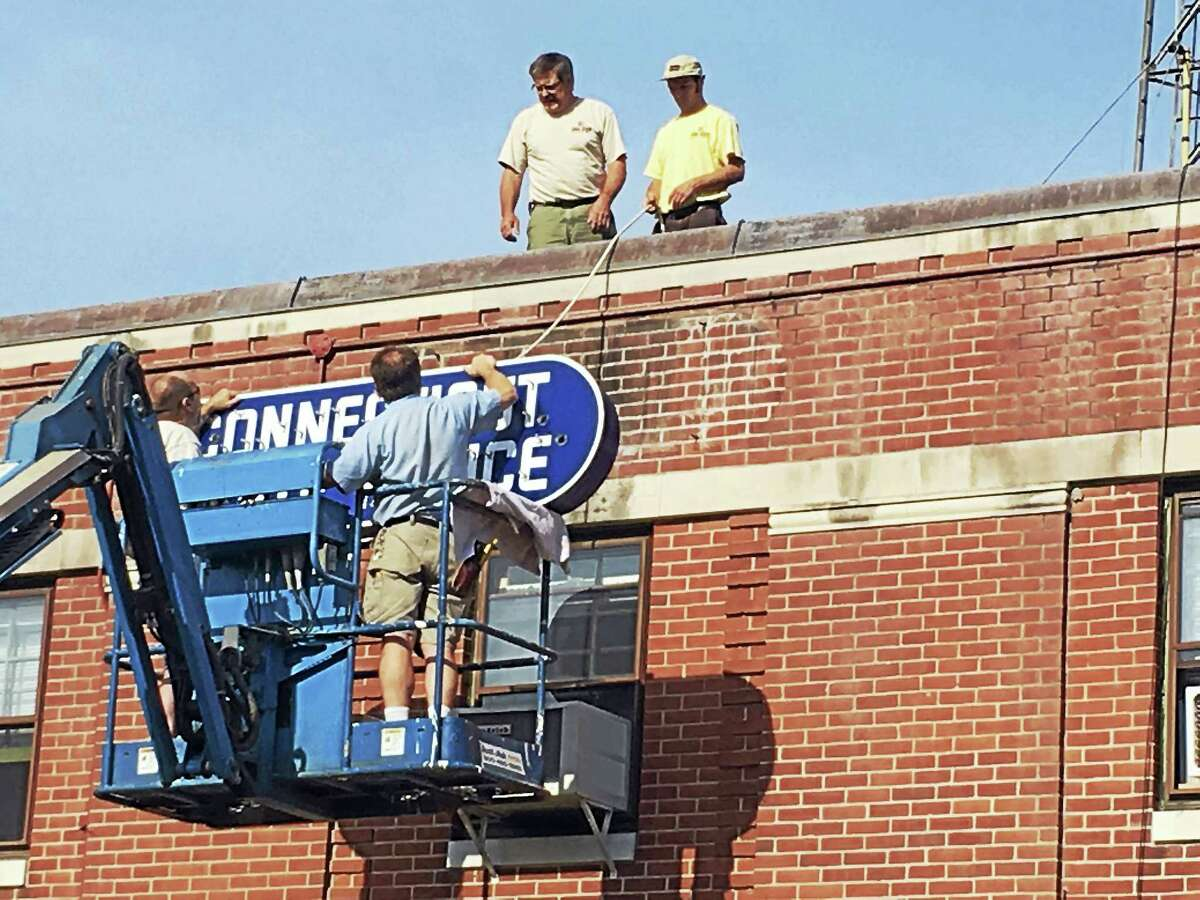CONTRIBUTED PHOTO The building sign at the Troop B headquarters in North Canaan was recently restored, according to Lt. William Baldwin. In the basket are Gary Rovelto and Frank Ghi. On the roof are Phil Ghi and Dominic Ghi. The restoration was funded by donations from the community.