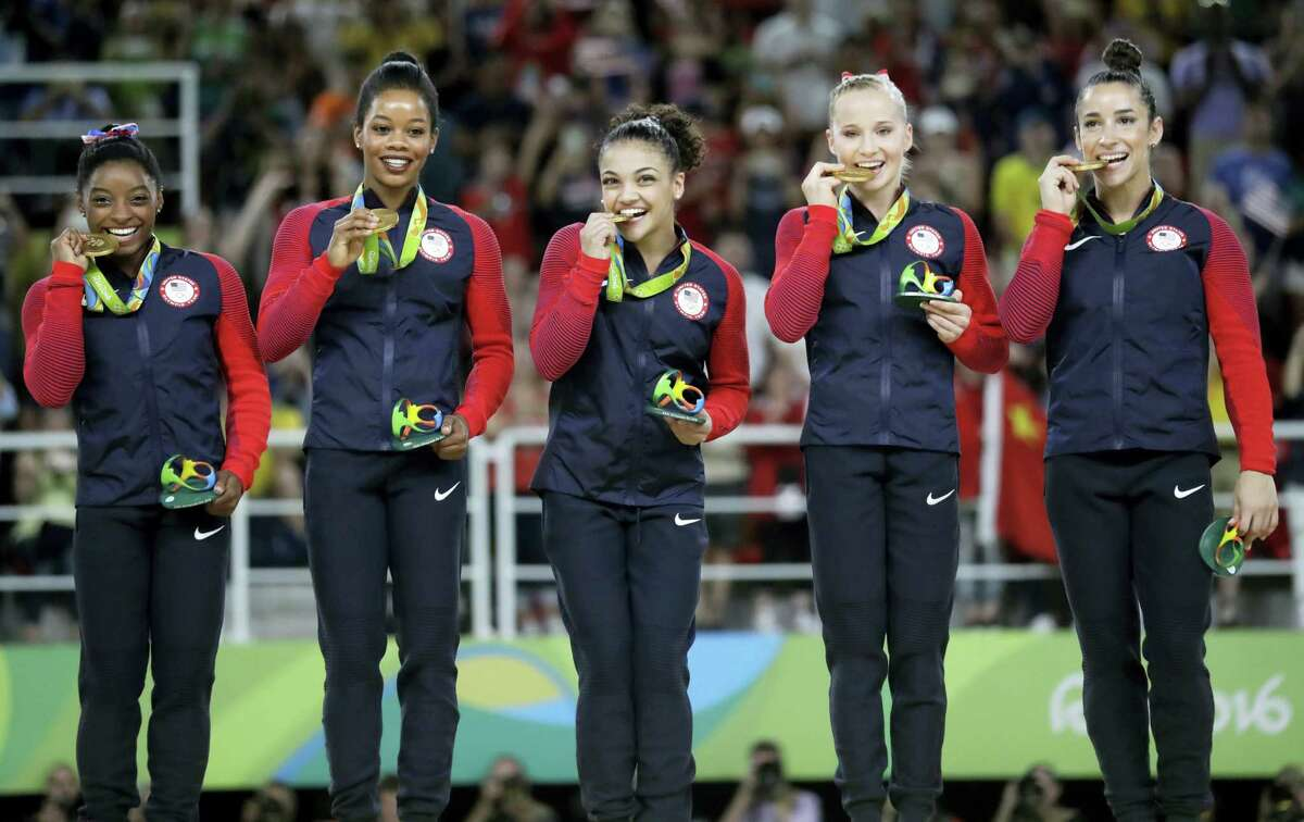 From left, U.S. gymnasts Simone Biles, Gabrielle Douglas, Lauren Hernandez, Madison Kocian and Aly Raisman hold their gold medals during the medal ceremony on Tuesday.
