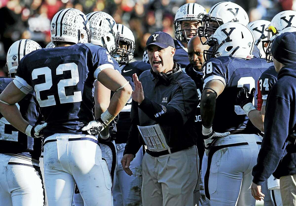 Yale head coach Tony Reno, center, talks to his team during last year's game against Harvard.