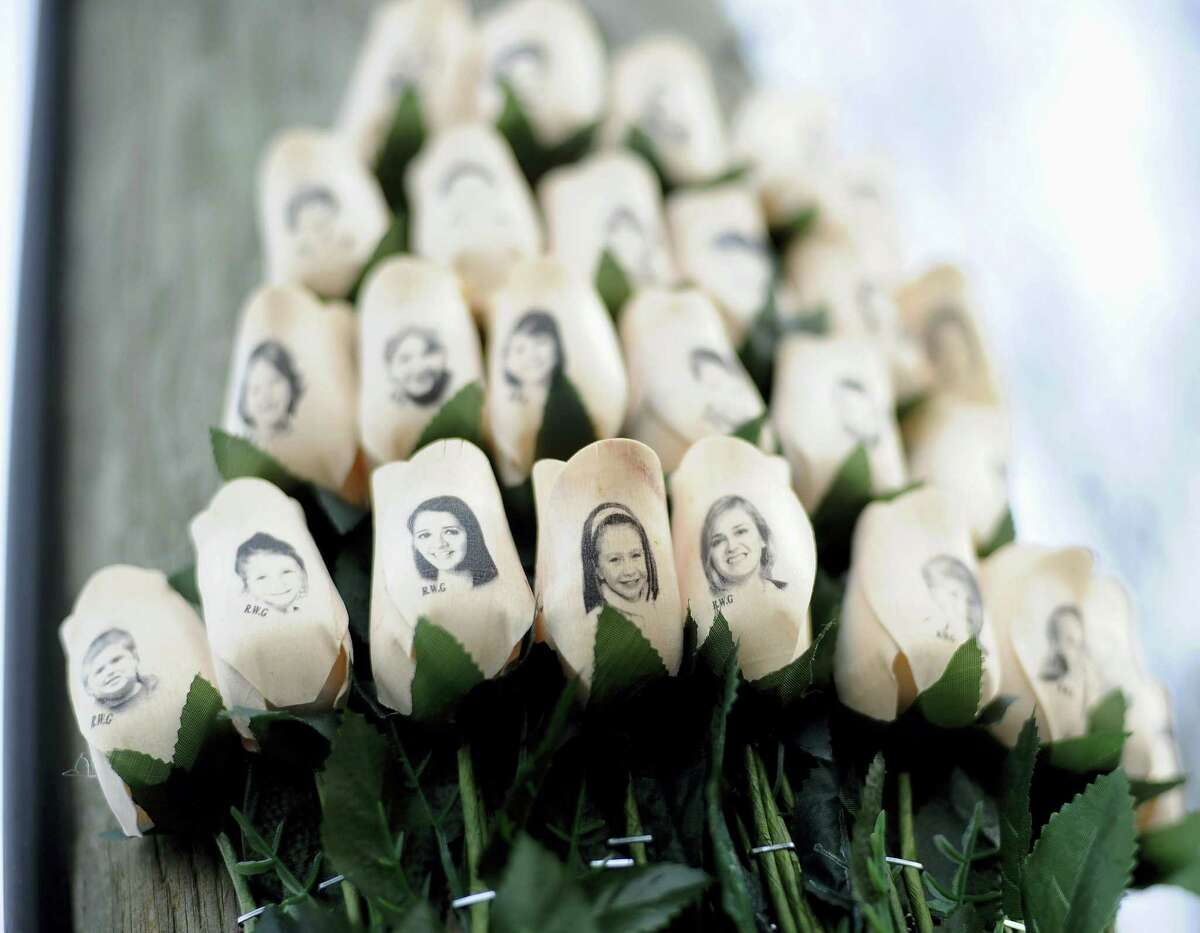 White roses with the faces of victims of the Sandy Hook Elementary School shooting are attached to a telephone pole near the school on the one-month anniversary of the shooting that left 26 dead in Newtown.