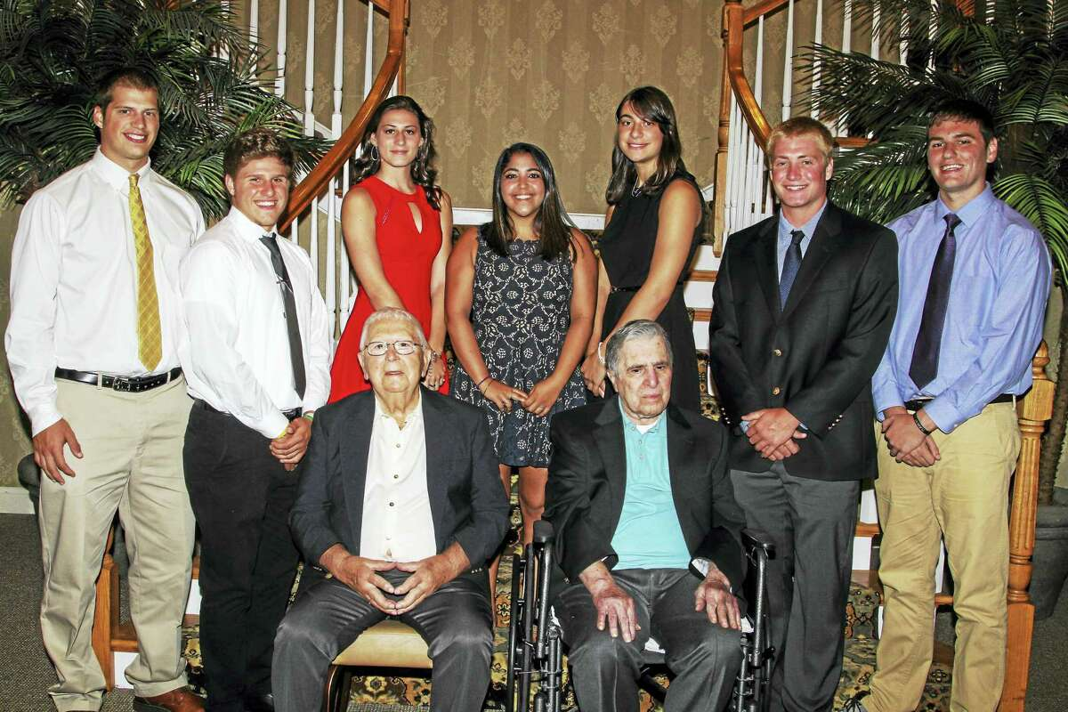 Photo by Marianne KillackeyBoard members Lou Zanderigo and Andy Pace, among the earliest members of the 71-year-old Torrington Varsity Alumni Club, sit in front of this year's club scholarship winners, standing left to right: Nate Bresson, Zak Mancini, Ashlynn Cook, Sima El-Ayoub, Casey Saade, Connor Finn and Matt Calabrese.