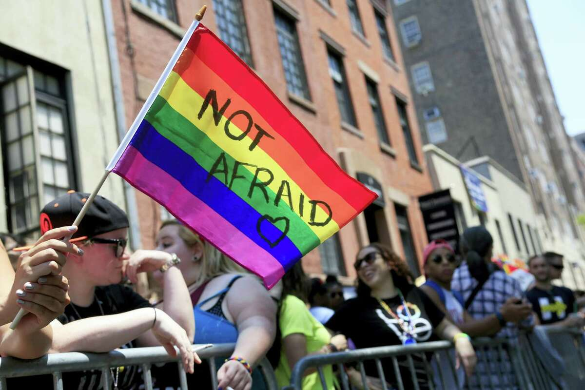 In this June 26, 2016 photo, a woman holds a rainbow flag during the NYC Pride Parade in New York. Young Americans overwhelmingly say they support LGBT rights when it comes to employment, health care and adoption, according to a new GenForward survey.