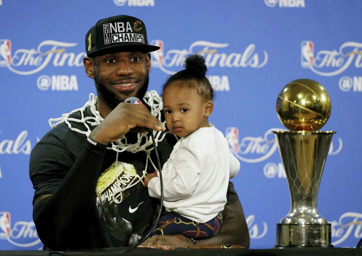 In this June 19, 2016 photo, Cleveland Cavaliers' LeBron James answers questions as he holds his daughter Zhuri during a post-game press conference after winning the NBA title by defeating the Golden State Warriors in the NBA Finals.