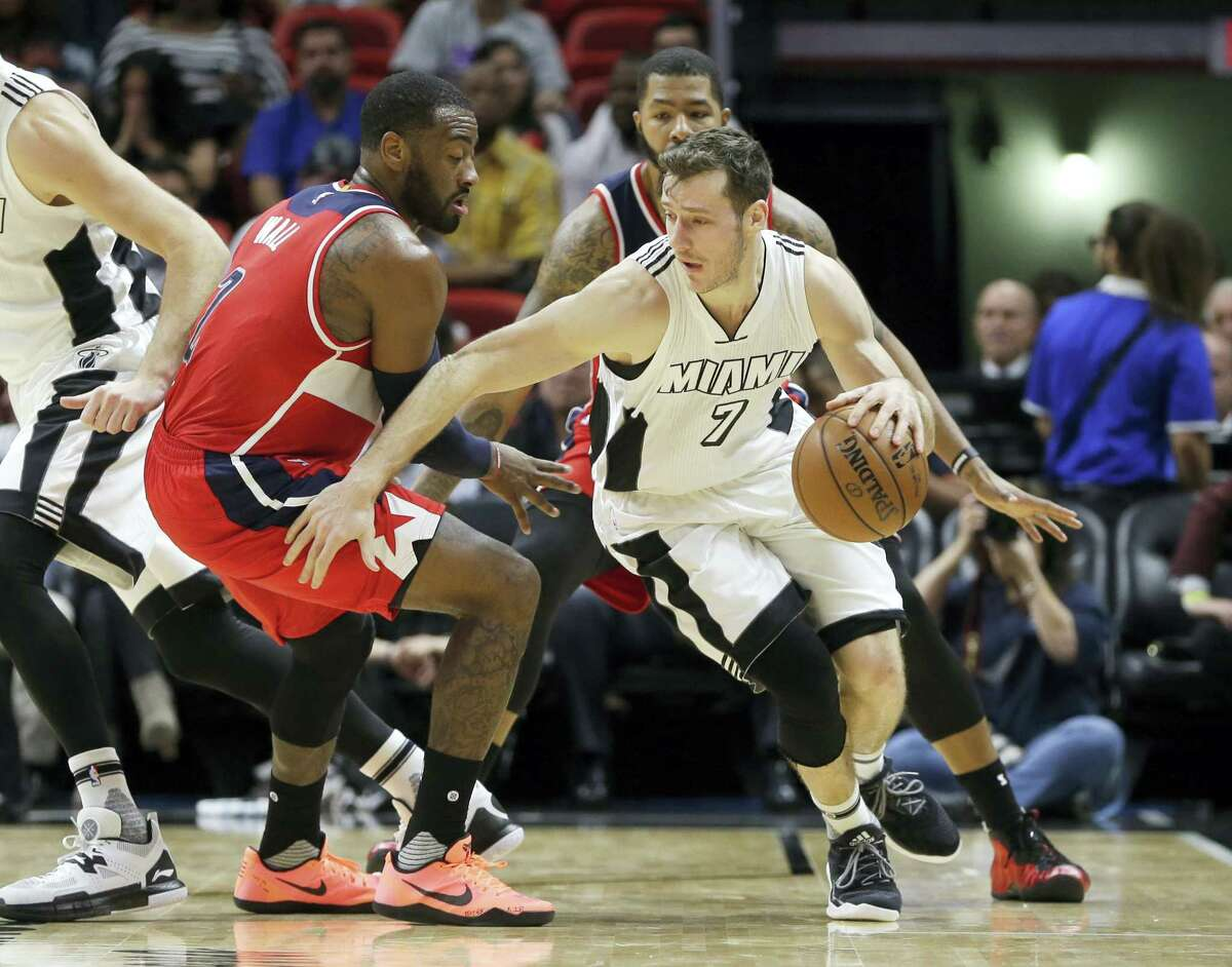 Miami Heat guard Goran Dragic (7) drives as Washington Wizards guard John Wall (2) defends in the first half of an NBA basketball game Dec. 12, 2016 in Miami.