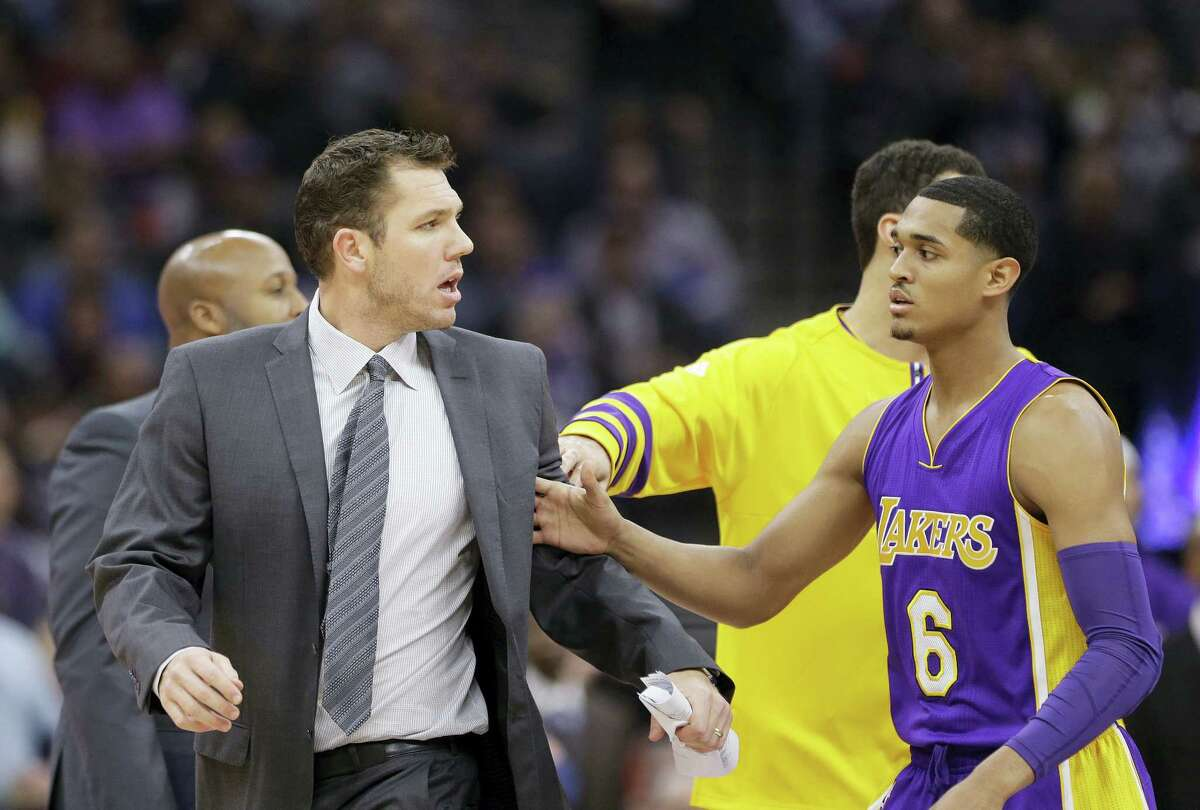 Los Angeles Lakers guard Jordan Clarkson, right, tries to guide Lakers head coach Luke Walton, left, to the locker room after he was ejected when he received two technical fouls during the first quarter of an NBA basketball game against the Sacramento Kings Dec. 12, 2016 in Sacramento, Calif.