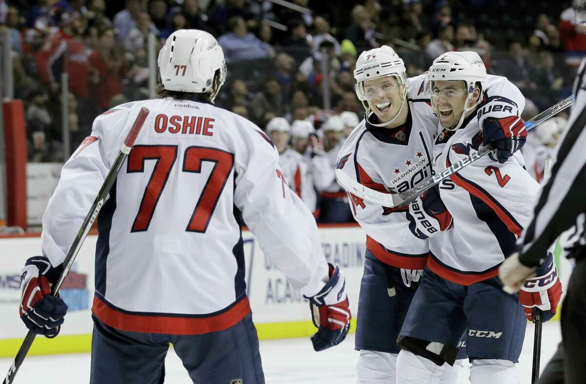 Washington Capitals' Matt Niskanen, right, John Carlson, center, and T.J. Oshie (77) celebrate after Niskanen scored a goal during the third period against the New York Islanders Tuesday. The Capitals won 4-2.