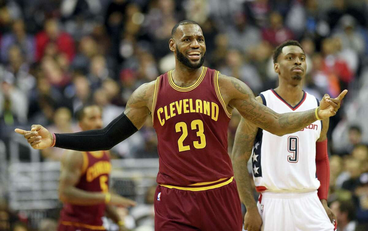 In this Nov. 11, 2016, file photo, Cleveland Cavaliers forward LeBron James (23)) gestures next to Washington Wizards guard Sheldon McClellan (9) during the second half of an NBA basketball game in Washington. The Cavaliers won 105-94. Now James is seen wearing a safety pin on the Dec. 19, 2016, cover of Sports Illustrated.