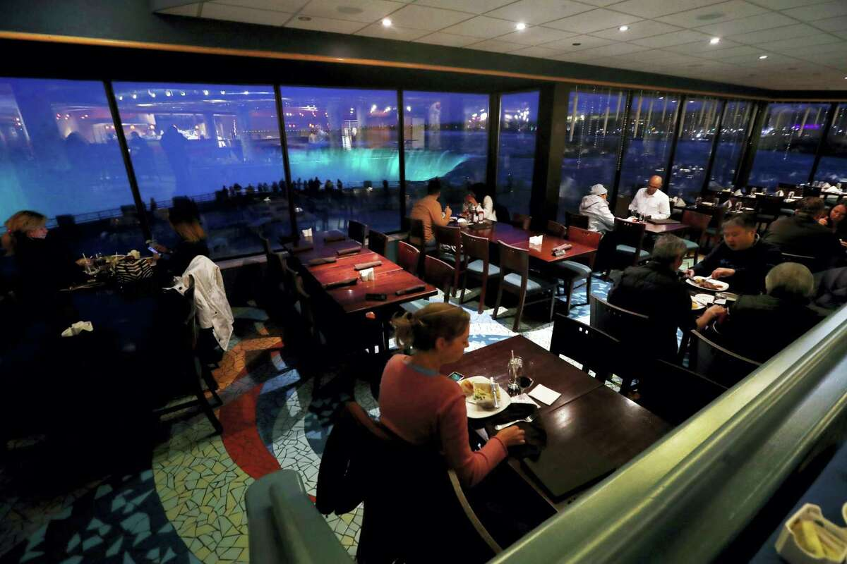 In this Saturday, Dec. 10, 2016, photo, people dine at the Elements Cafe overlooking the Niagara Falls illuminated by new LED lights, in Niagara, Ontario. Visitors unwilling to brave the frigid air outdoors can watch Niagara Falls illuminated after dark from the windows of hotels and restaurants on the Canadian shore.