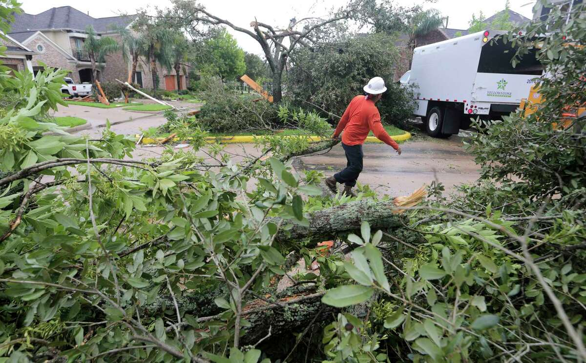 Abel Carre'o of Yellowstone Landscaping clears downed branches in the Sienna Plantation community in Missouri City. Early Saturday morning, Hurricane Harvey spawned a tornado believed responsible for damage to as many as 50 homes in the area.