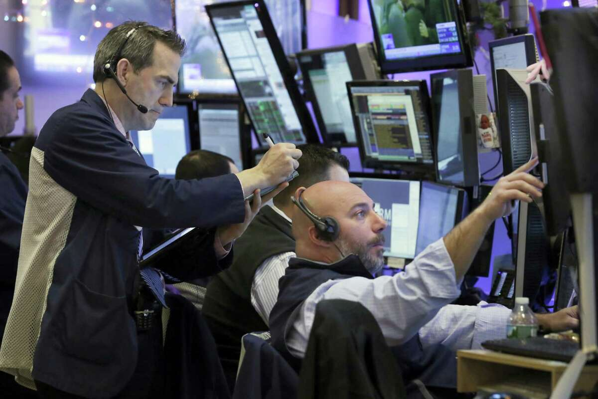 Traders work in their booth on the floor of the New York Stock Exchange Tuesday.