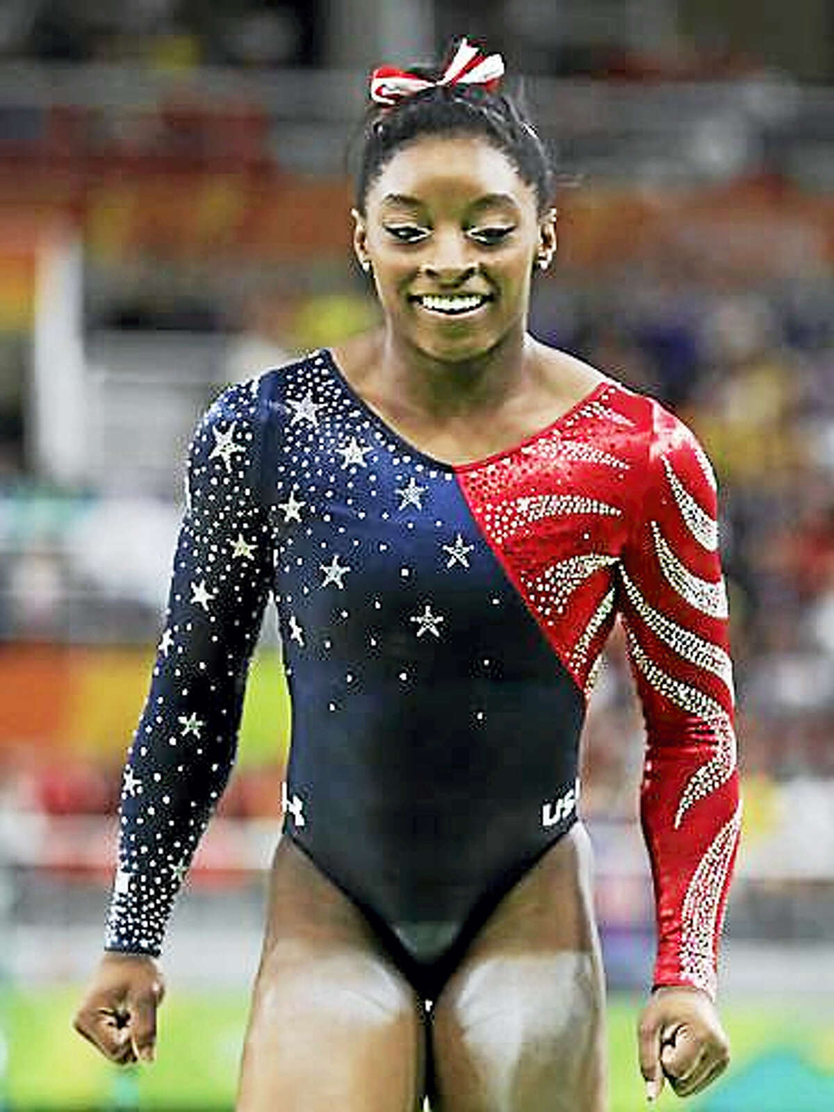 United States' Simone Biles celebrates after completing her routine on the balance beam during the artistic gymnastics women's qualification at the 2016 Summer Olympics in Rio de Janeiro, Brazil, Sunday, Aug. 7, 2016.