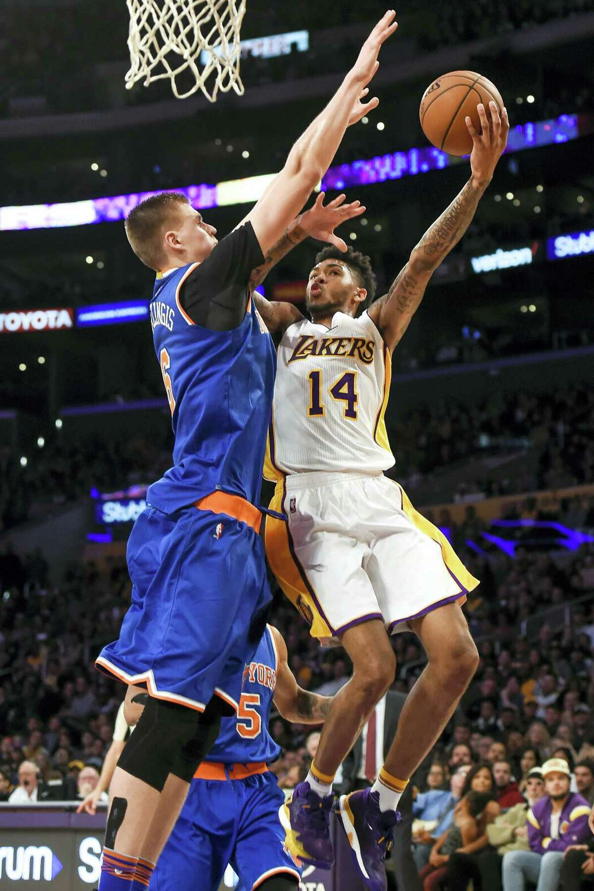 Los Angeles Lakers forward Brandon Ingram (14) battles New York Knicks forward Kristaps Porzingis (6), of Latvia, as he drives to the basket during the second half of an NBA basketball game on Sunday, Dec. 11, 2016 in Los Angeles. The Knicks win 118-112.