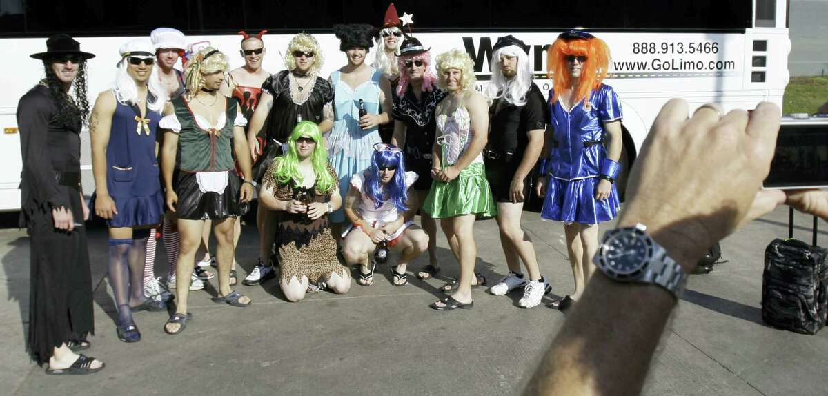 Oakland Athletics rookie players dressed in costumes line up for a group photo before boarding the team bus.