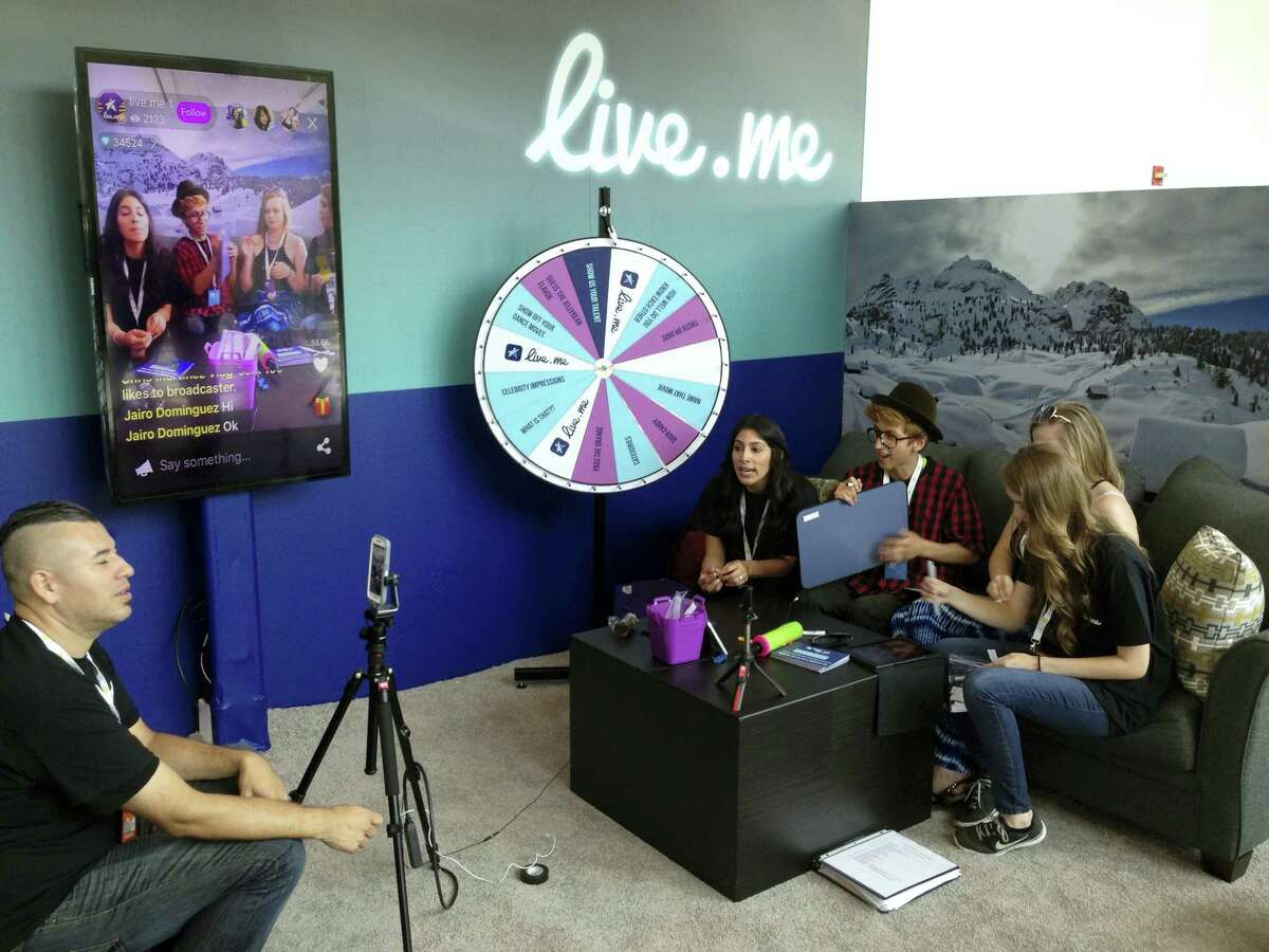In this June 23, 2016 photo, Erick Armas, left, captures video of, from right, Jordan Hoyle, Violet Summersby, George Padilla and Sue Evelyn Gil, who were live broadcasting from the live.me booth at VidCon, an annual convention for the fans of stars from YouTube, Vine, Instagram and other video platforms, at the Anaheim Convention Center in Anaheim Cailf.