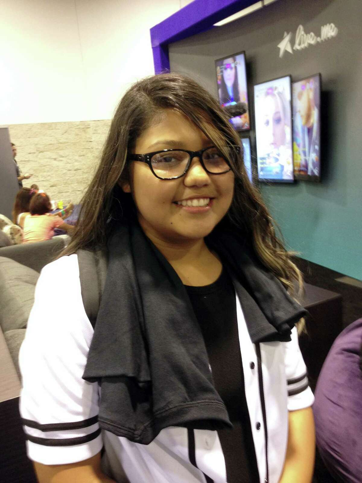In this Thursday, June 23, 2016, photo, Sandra Alvarez poses for a photo in front of the live.me booth at VidCon, the annual online video convention at the Anaheim Convention Center, in Anaheim, Calif. Alvarez said she used to spend $50 a month, more than half her allowance, tipping broadcasters on YouNow. (AP Photo/Ryan Nakashima)