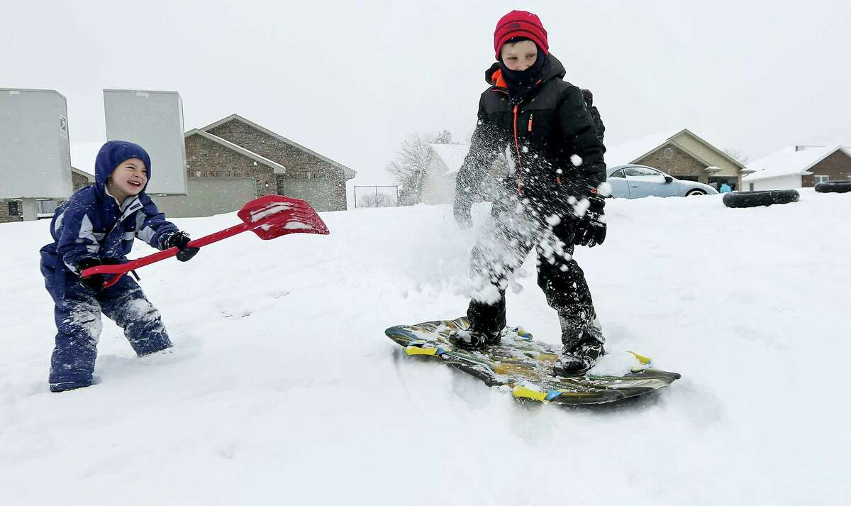 Austin Ricks, 4, left, throws snow on Brandon Grimes, 9, while they play in the snow in Asbury, Iowa, on Dec. 11, 2016. Dubuque, Iowa, received 4 inches of snow overnight, less than forecasters had expected.