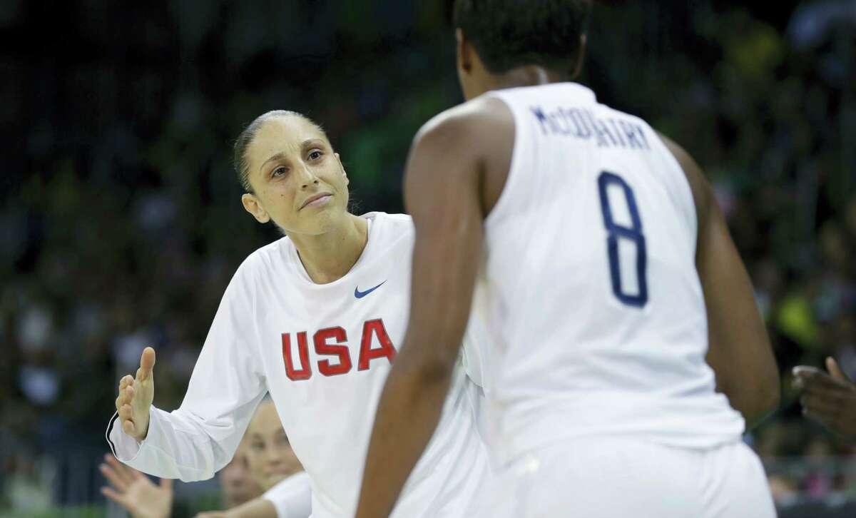 United States guard Diana Taurasi greets teammate Angel McCoughtry after a play during the second half on Sunday.