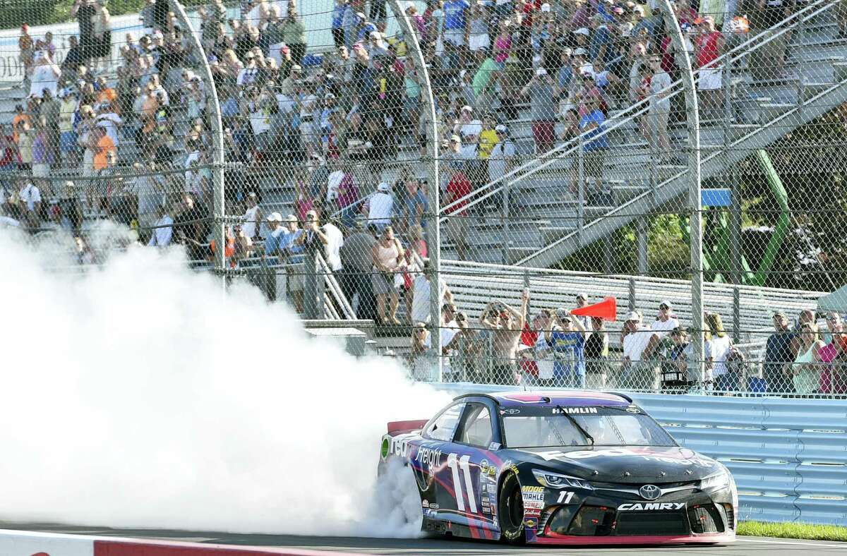 Denny Hamlin celebrates with a burnout after winning at Watkins Glen International on Sunday in Watkins Glen, N.Y.