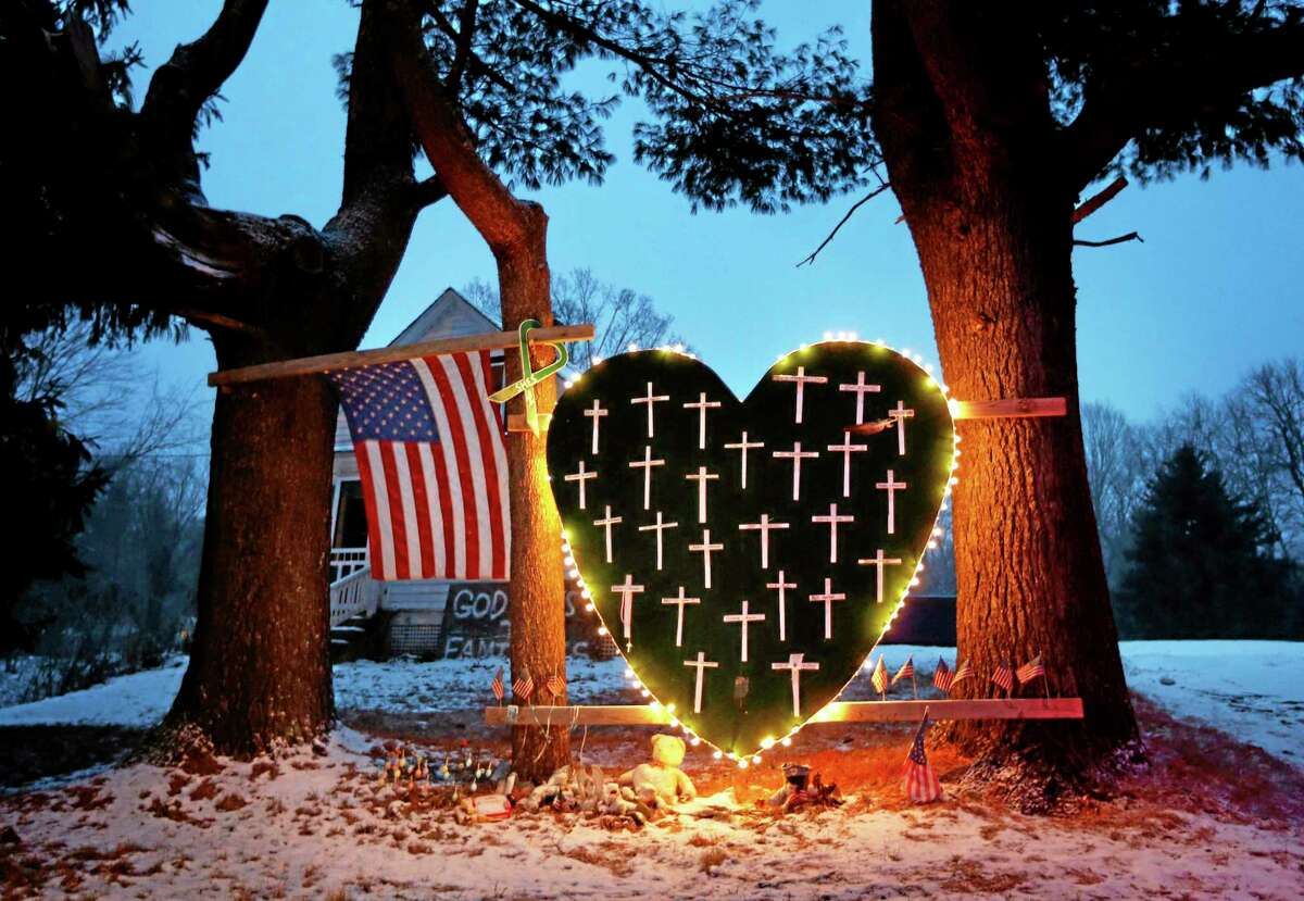 A makeshift memorial with crosses for the victims of the Sandy Hook massacre stands outside a home in Newtown on Dec. 14, 2013, the one-year anniversary of the shootings.