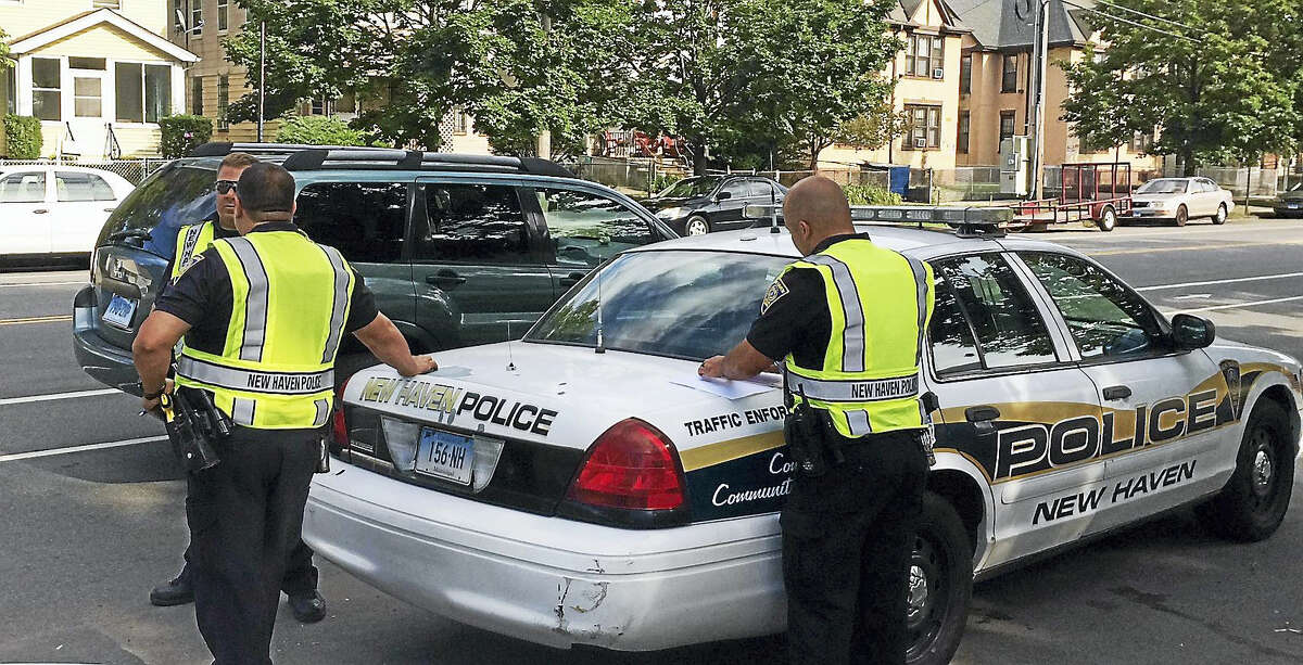 New Haven police officers work a distracted driving checkpoint Aug. 9, 2016 in front of Amistad High School on Dixwell Avenue. New Haven police, along with state troopers and several other towns, are cracking down on distracted driving over two weeks in August.