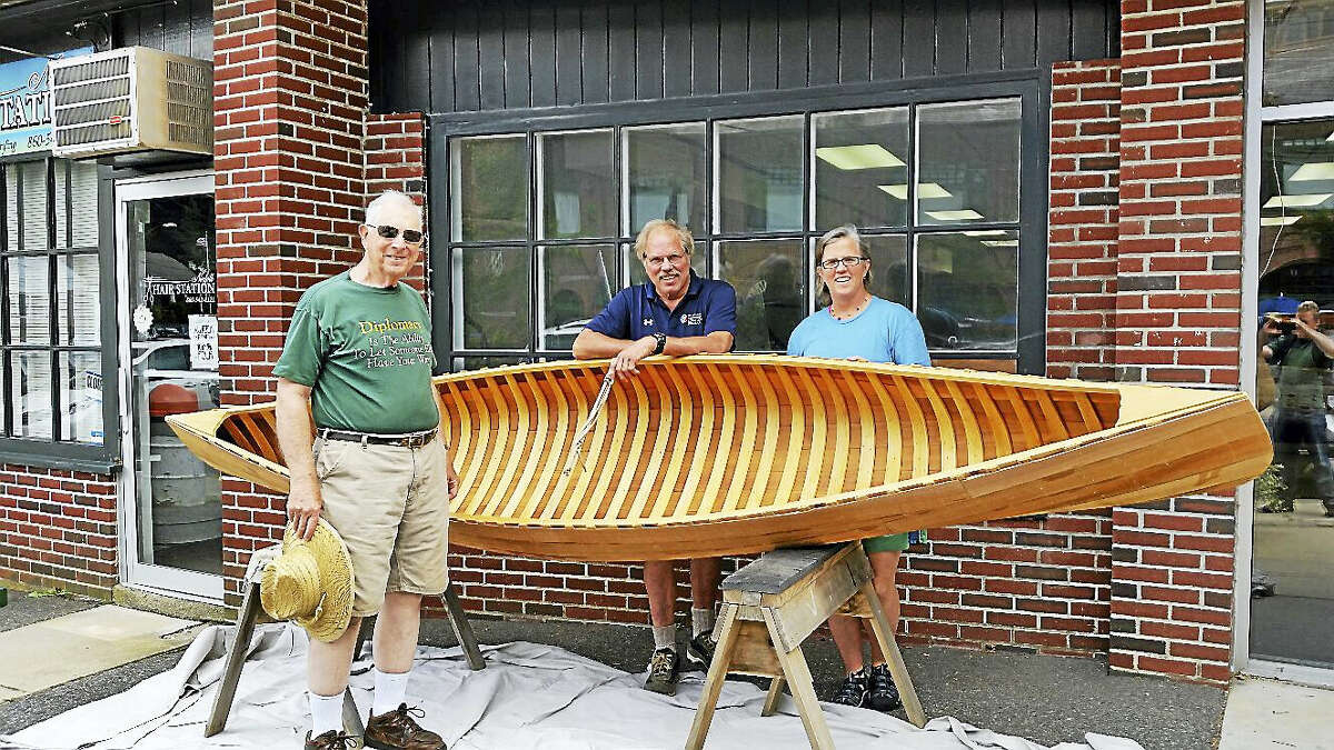 N.F. Ambery photo Customer Everett Briggs of Norfolk pauses with Schuyler Thomson and Abby Burbank of Norfolk Boatworks at their temporary space at 2 Station Place in Norfolk.