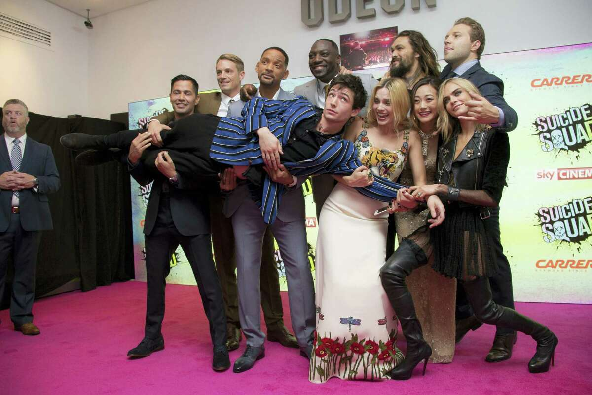 Actors, from centre left to right, Jay Hernandez, Joel Kinnaman, Will Smith, Adewale Akinnuoye, Margot Robbie, Jason Momoa, Karen Fukuhara, Jai Courtney and Cara Delevingne hold Ezra Matthew Miller, upon arrival at the European Premiere of Suicide Squad, at a central London cinema in Leicester Square on Aug 3, 2016.