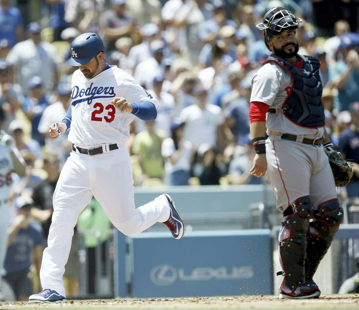 The Dodgers' Adrian Gonzalez, left, scores on a single by A.J. Ellis in the second inning.