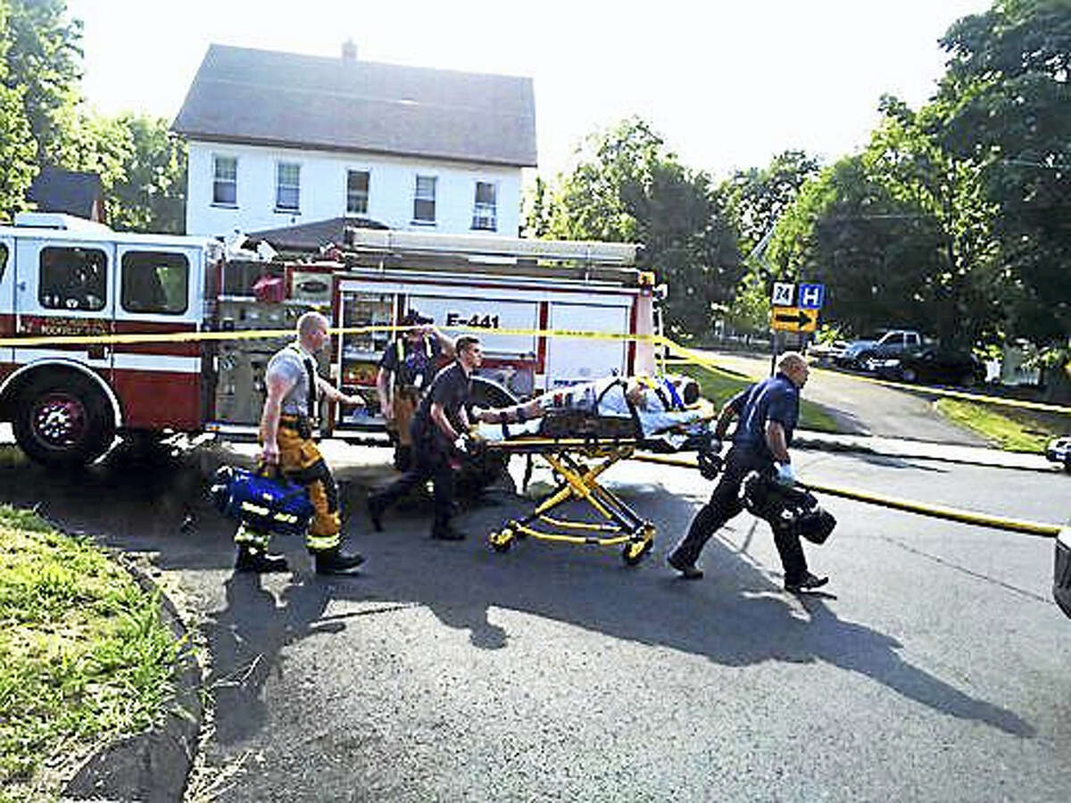 First responders help an injured person after a house explosion in Vernon on Thursday.