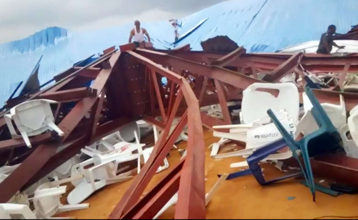 In this image made from video taken on Dec. 10, 2016, local people survey the scene after a church roof collapsed in Uyo, Nigeria. Metal girders and the roof of a crowded church collapsed onto worshippers in southern Nigeria, killing at least 160 people with the toll likely to rise, a hospital director said Sunday. Mortuaries in the city of Uyo are overflowing from Saturday's tragedy, medical director Etete Peters of the University of Uyo Teaching Hospital told The Associated Press.