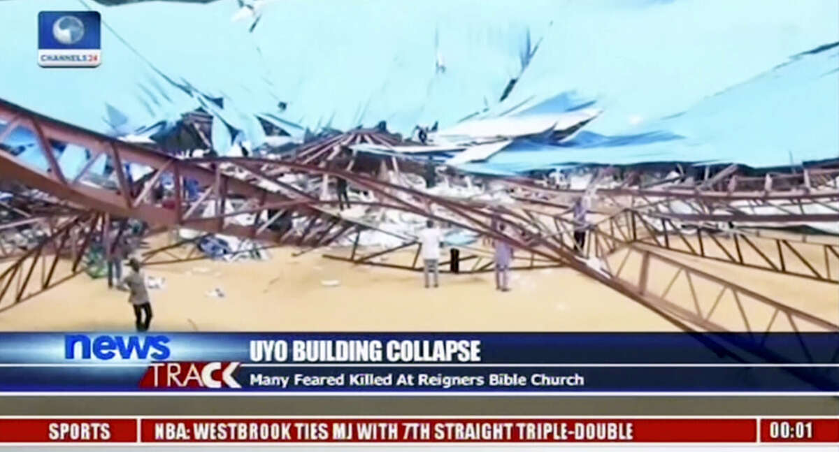 In this image taken from video, people stand at the scene after the roof of The Reigners Bible Church International collapsed onto worshippers in Uyo, southern Nigeria on Dec. 10, 2016 killing dozens, an official said.