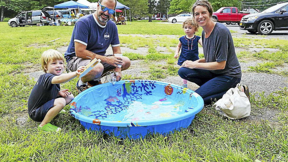 "Max Martins, 3, tried out a toy paddle boat he had made with his family during a ""Build a Paddle Boat"" workshop on Saturday morning at the Kent Farmer's Market as part of the Kent Sidewalk Festival, which continues Sunday."