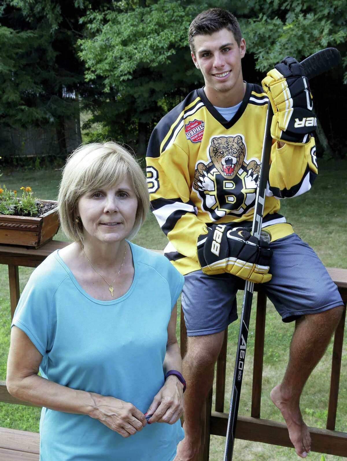 Debbie Amorelli poses with her son, Chris, 17, at their home in Upton, Mass. Debbie and her husband spend about $10,000 a year to pay for Chris to play hockey. They are able to pay for it thanks to an inheritance from his grandfather but keep telling him that this is money that could be going toward college.