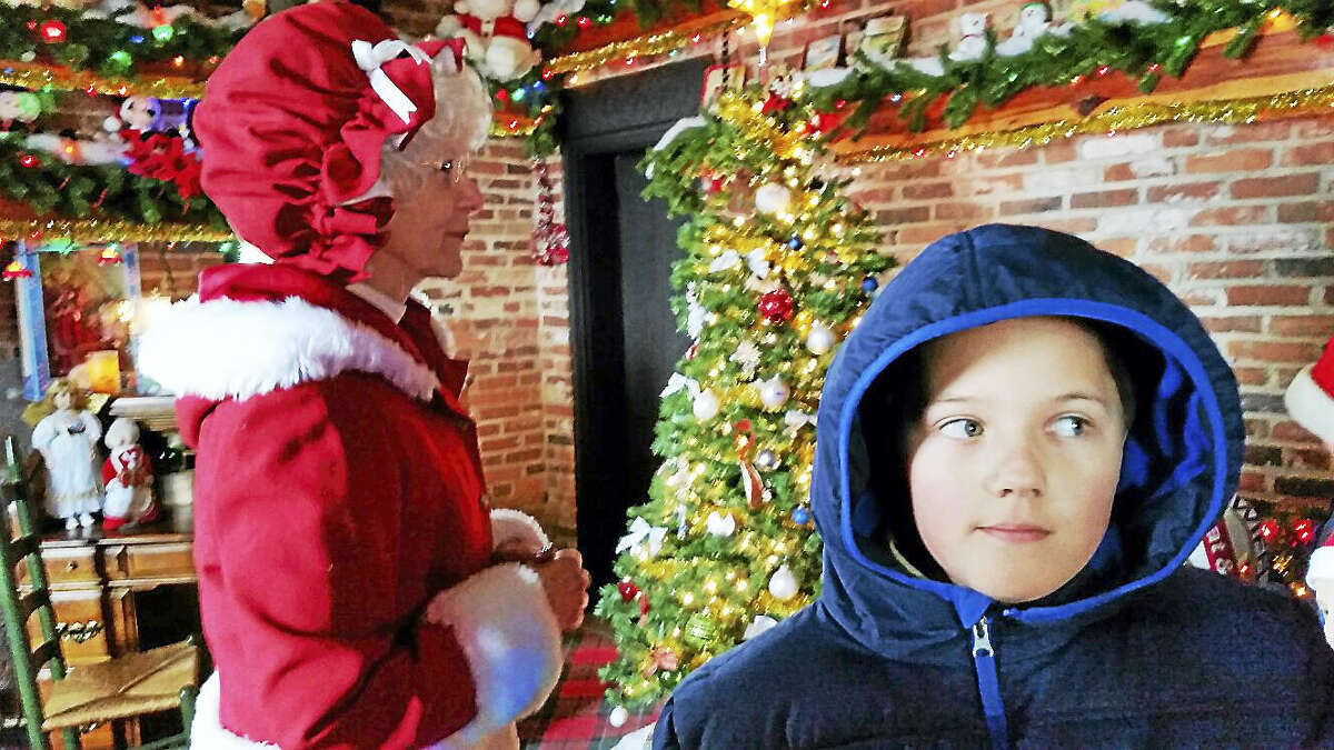 N.F. AMBERY PHOTO A child ponders the words of Mrs. Claus after a chat during the 69th edition of Carl Bozenski's Christmas Village.