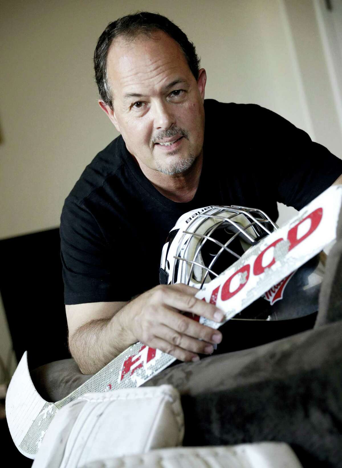 Tim Richmeier poses for a photo with some of his 15-year-old son's hockey equipment, in Phoenix. Richmeier was spending about $5,000 a season using his tax refunds, halting contributions to his 401(k), and putting travel expenses on a credit card, including $6,000 he's still paying off, so his son could play on a travel hockey team.
