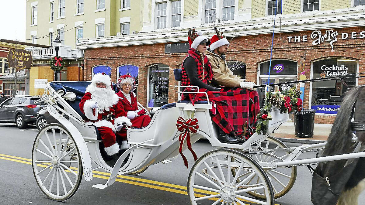 N.F. Ambery photo Santa and Mrs. Claus travel by a horse-drawn carriage Sunday in Torrington.