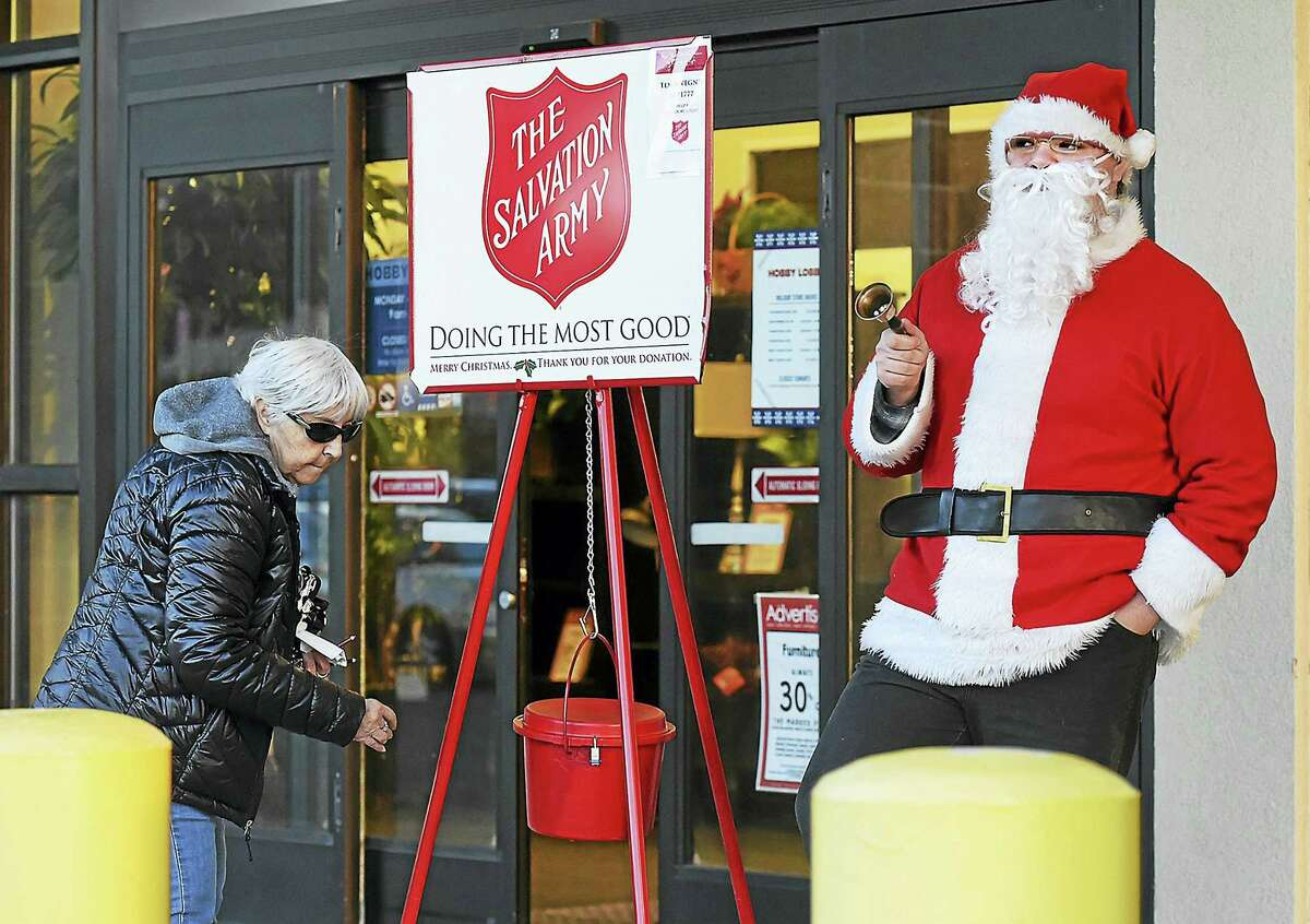 Catherine Avalone/New Haven Register Will Ruddell, son of New Haven Register reporter Pam McLoughlin helped spread holiday cheer as he volunteers last week for the Salvation Army Kettle Drive at Hobby Lobby in Milford. The Salvation Army is looking for volunteer bell ringers.