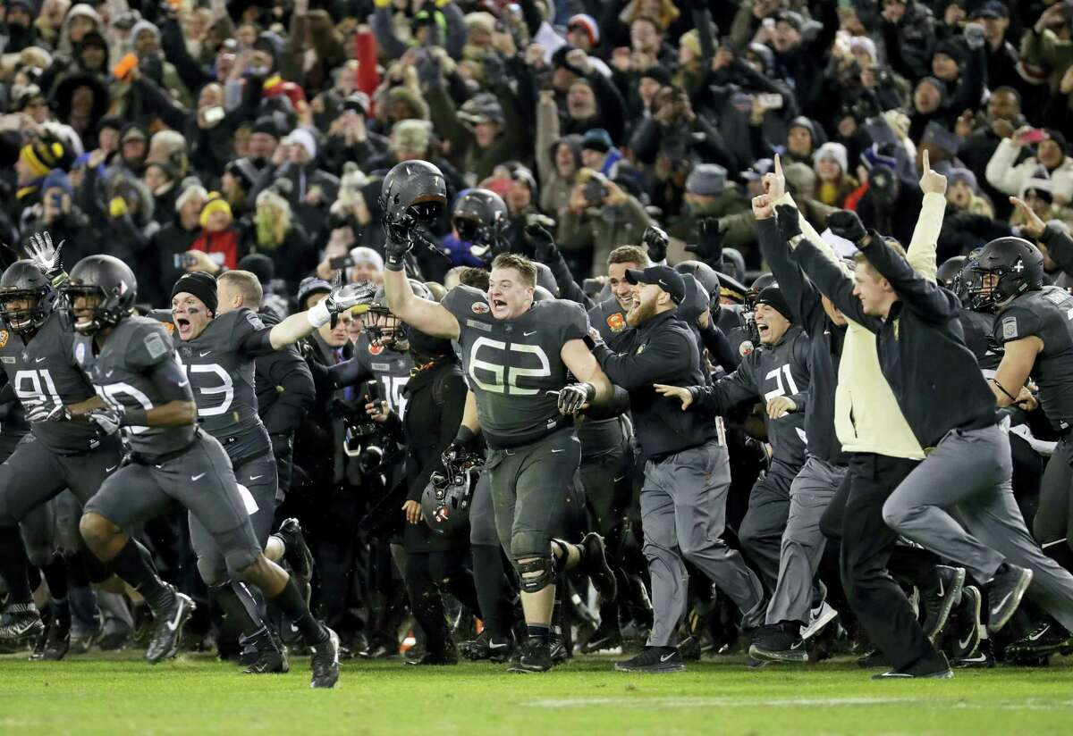 Army players and coaches run onto the field after beating Navy 21-17 in Baltimore on Saturday.