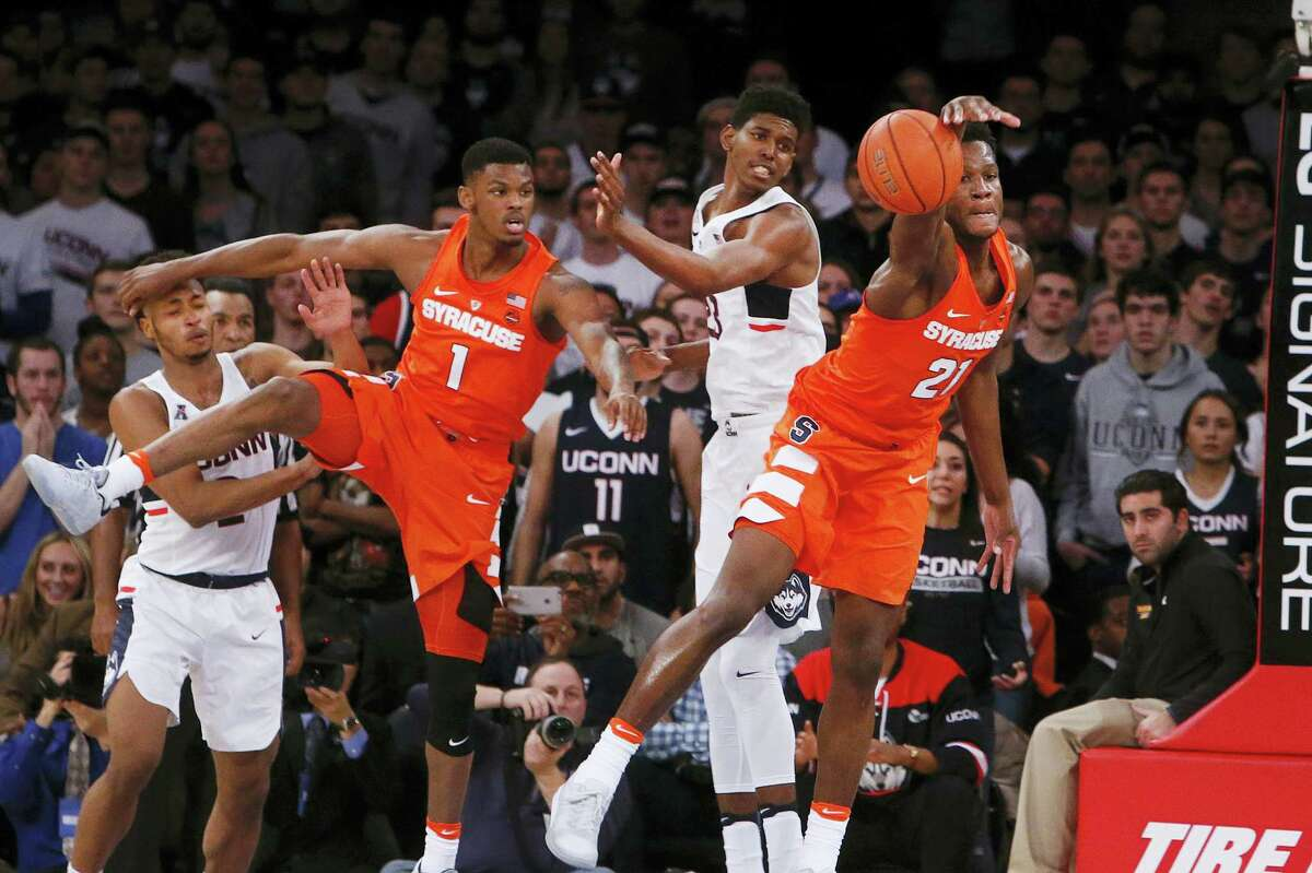 Syracuse's Tyler Roberson (21) grabs for a loose ball ahead of UConn's Juwan Durham, center, during their game on Monday.