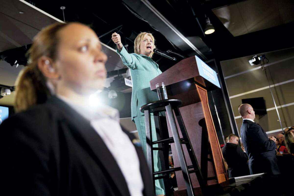 Members of the Secret Service stand guard near Democratic presidential candidate Hillary Clinton as she speaks at a rally at International Brotherhood of Electrical Workers Local 357 Hall, in Las Vegas, Thursday, Aug. 4, 2016, after an animal rights protester attempted to jump fencing during Clinton's speech.